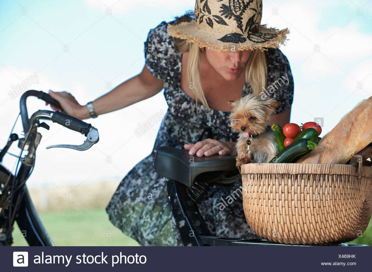 Mature woman on electric bike with dog and vegetables in basket Stock Photo