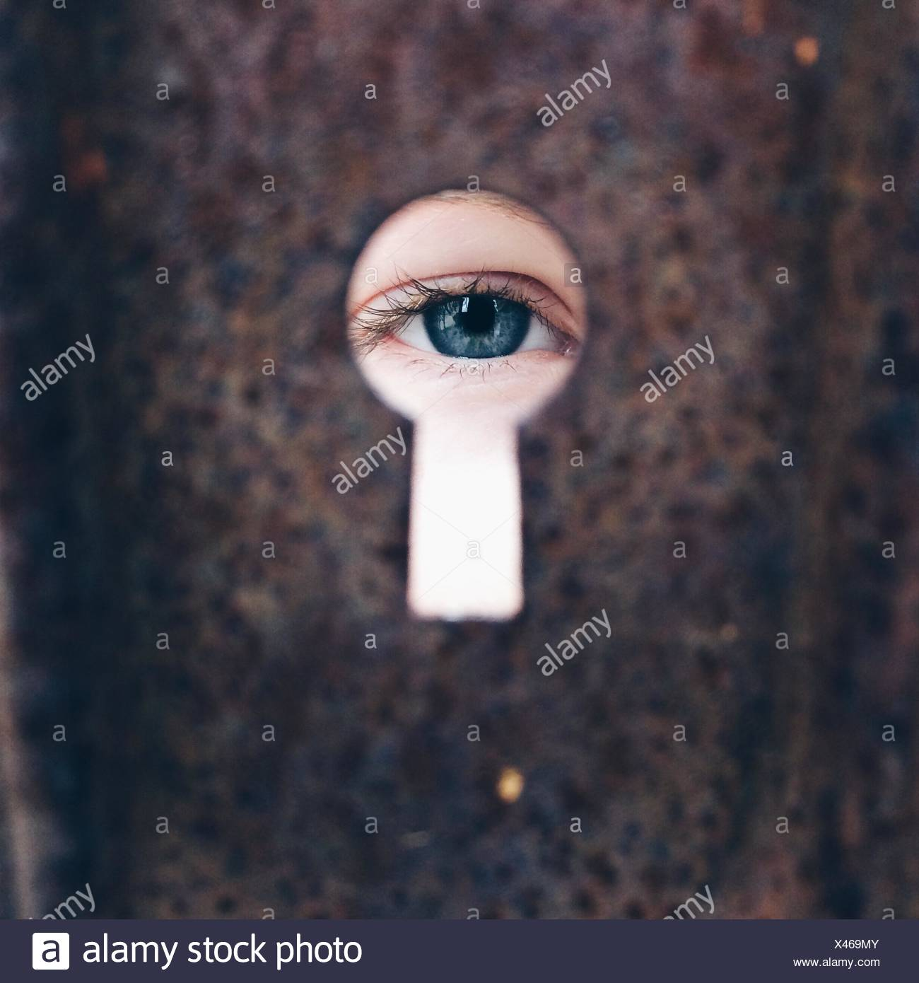 Girl (8-9)  looking through keyhole - Stock Image
