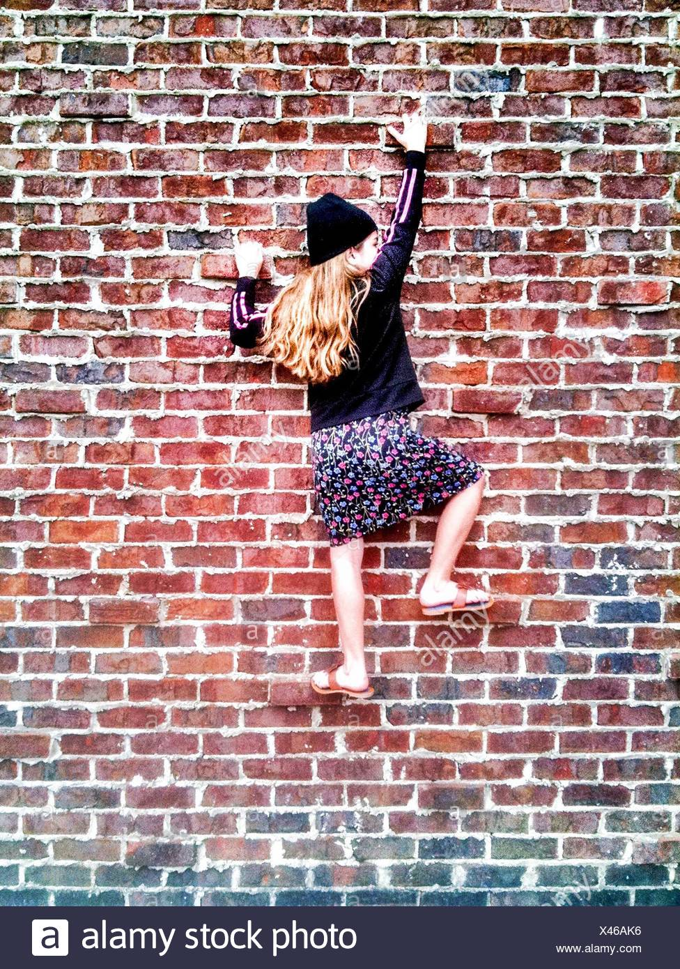 Full Length Rear View Of Girl Climbing On Brick Wall - Stock Image