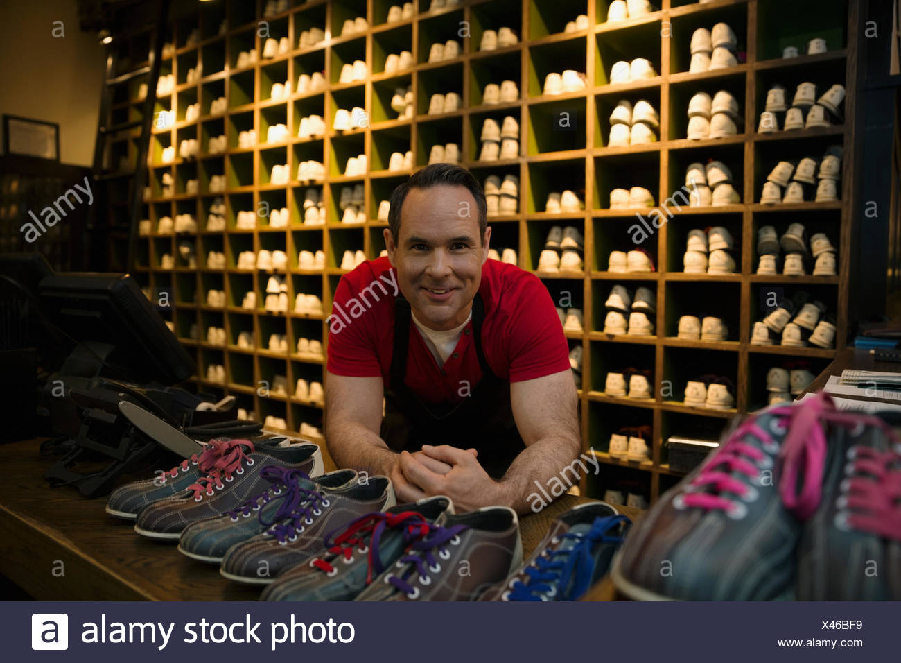 Portrait confident worker at bowling shoe rental counter - Stock Image