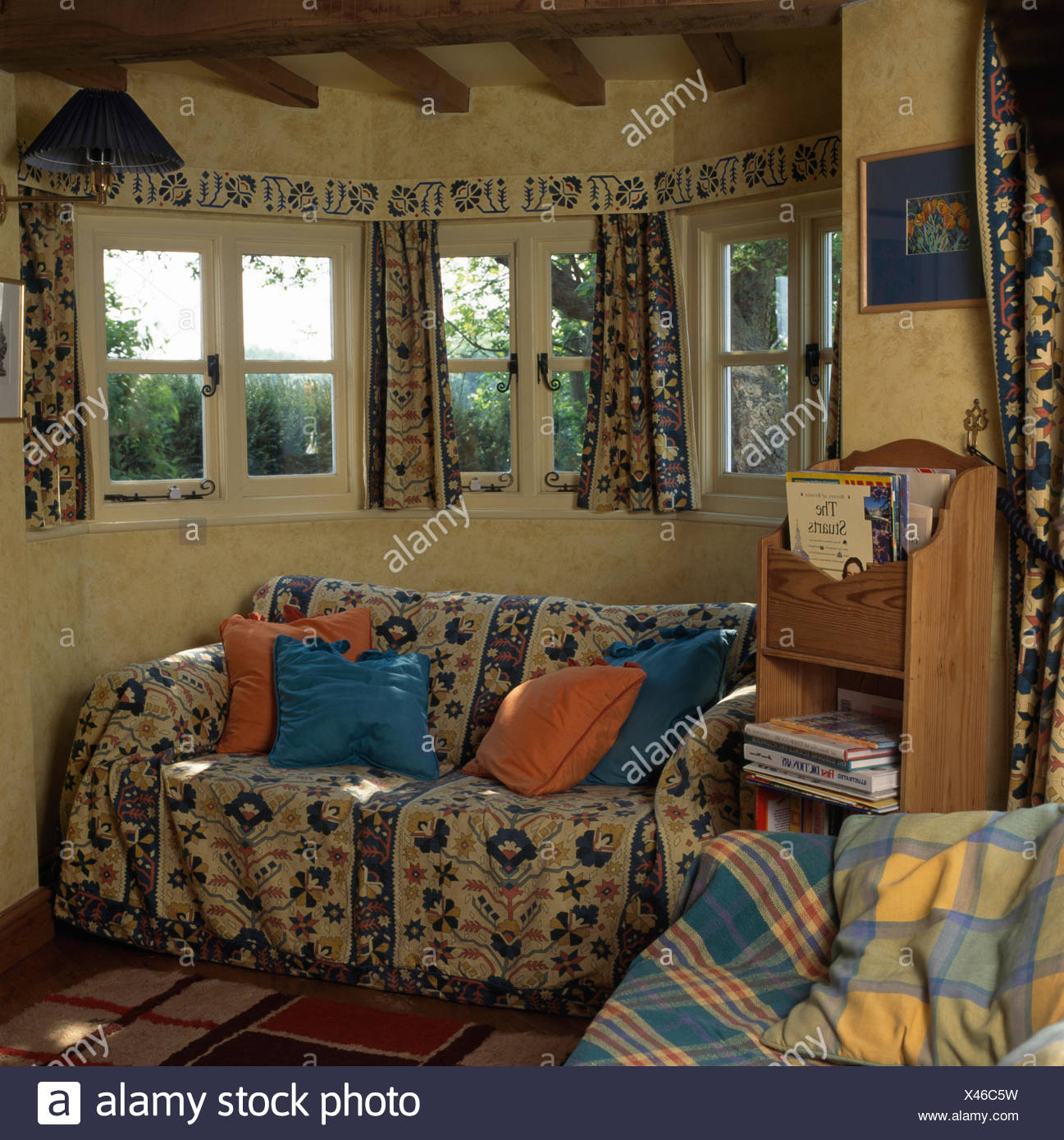 Floral patterned throw on sofa below windows in economy style cottage living room - Stock Image