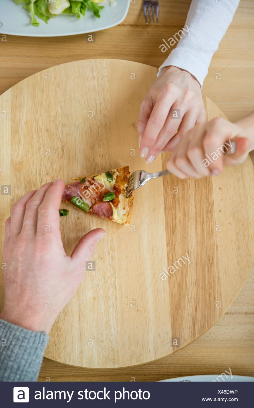 Family fighting for last slice of pizza - Stock Image