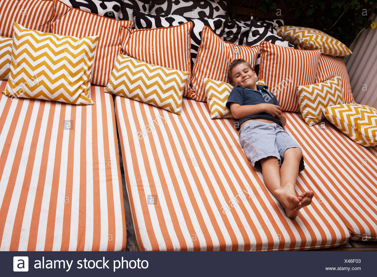 Boy relaxing on striped outdoor furniture with cushions - Stock Image