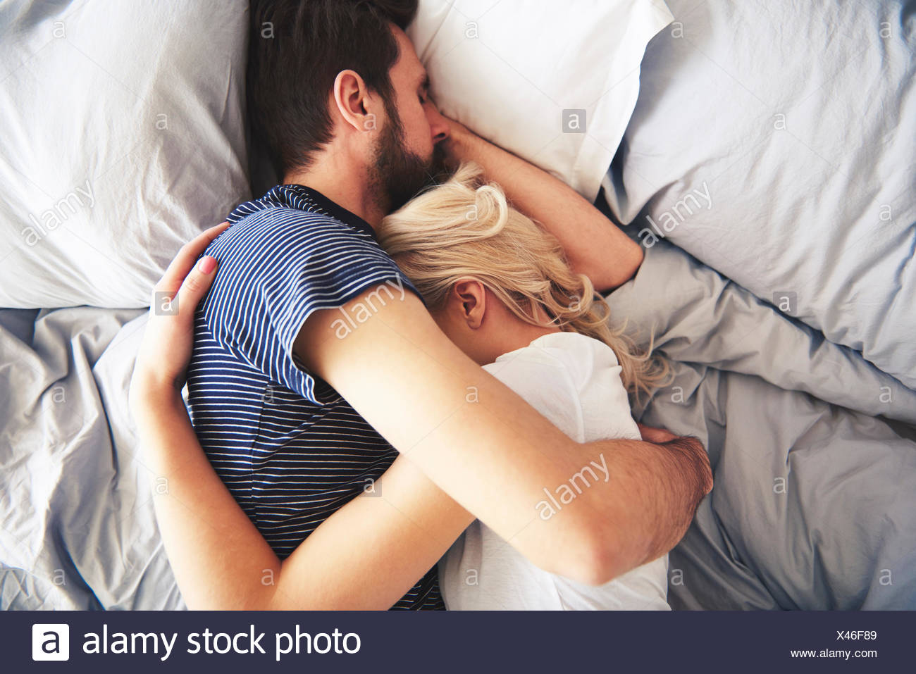 Couple lying in bed together, sleeping, arms around each other - Stock Image