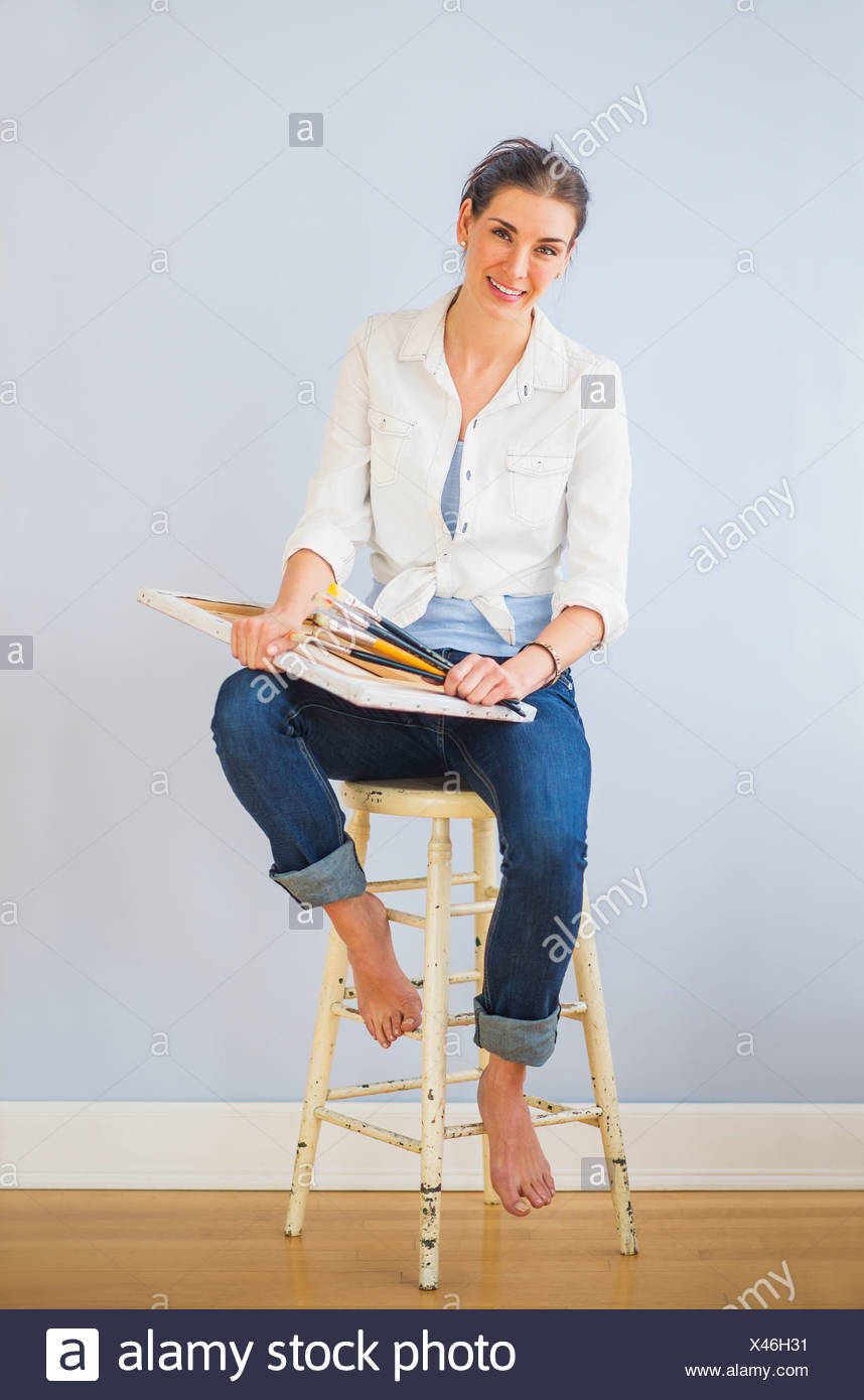 Studio Shot of woman sitting on stool, holding paintbrushes and artist's canvas - Stock Image