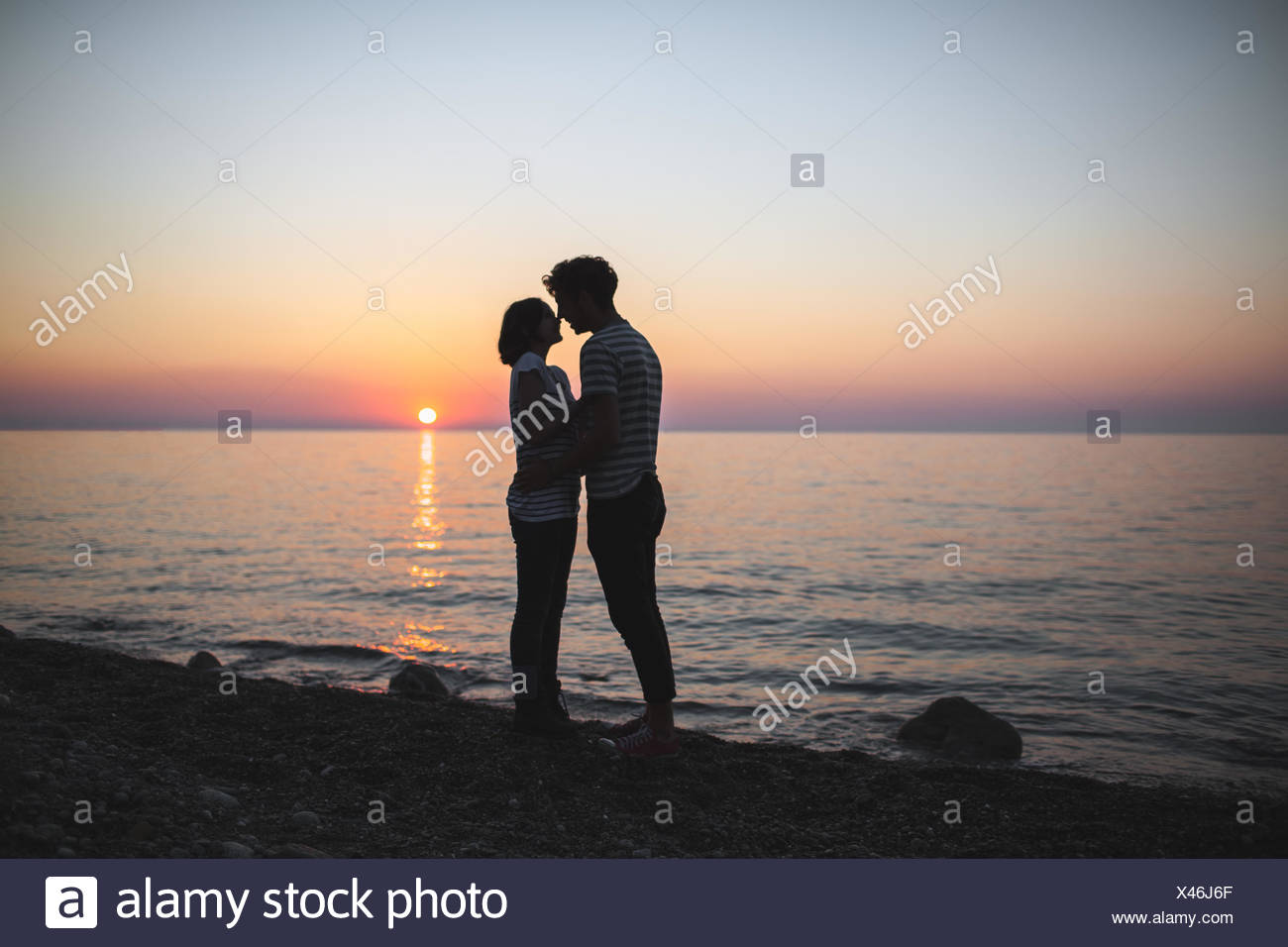 Teenagers (14-15) hugging each other at sunset Stock Photo