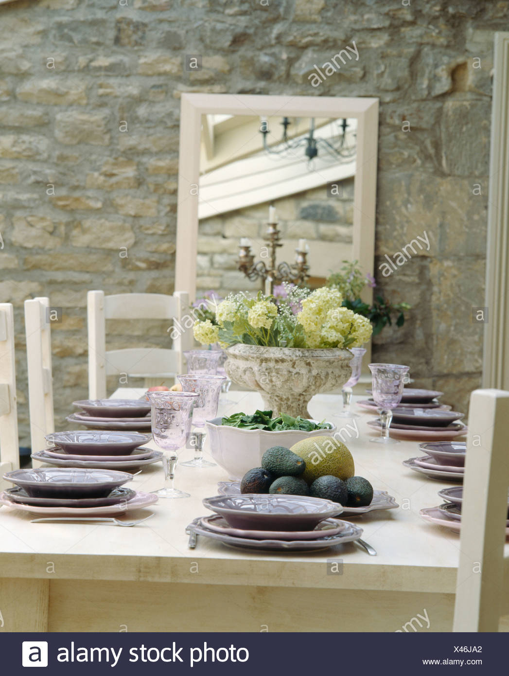 Mauve Plates On Cream Table Set For Lunch In Country Dining Room With Cream Framed Mirror On Exposed Stone Wall Stock Photo Alamy