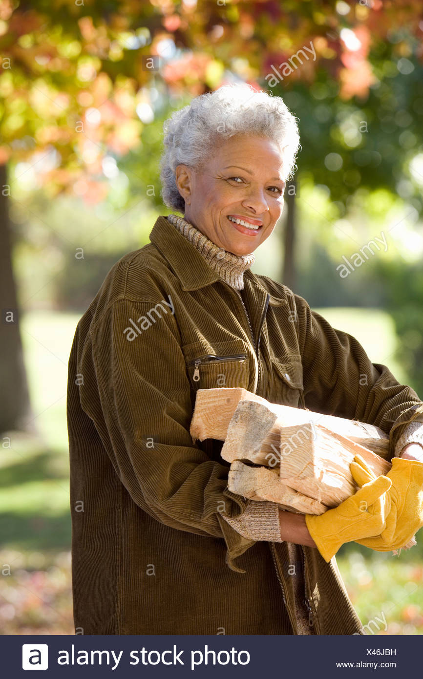 Senior woman collecting firewood in autumn garden smiling side view portrait - Stock Photo