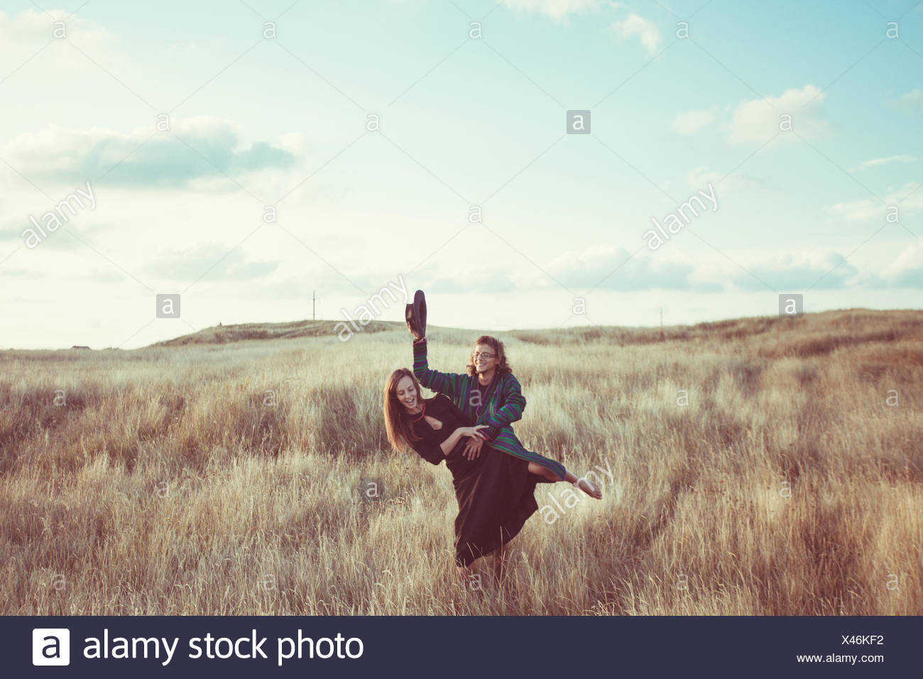 Couple messing about in field - Stock Image