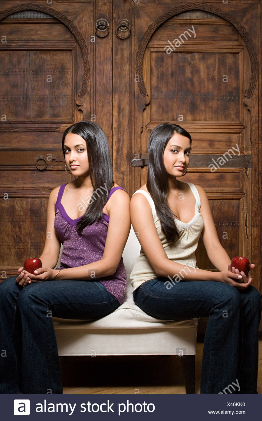 Indian sisters sharing a chair - Stock Image