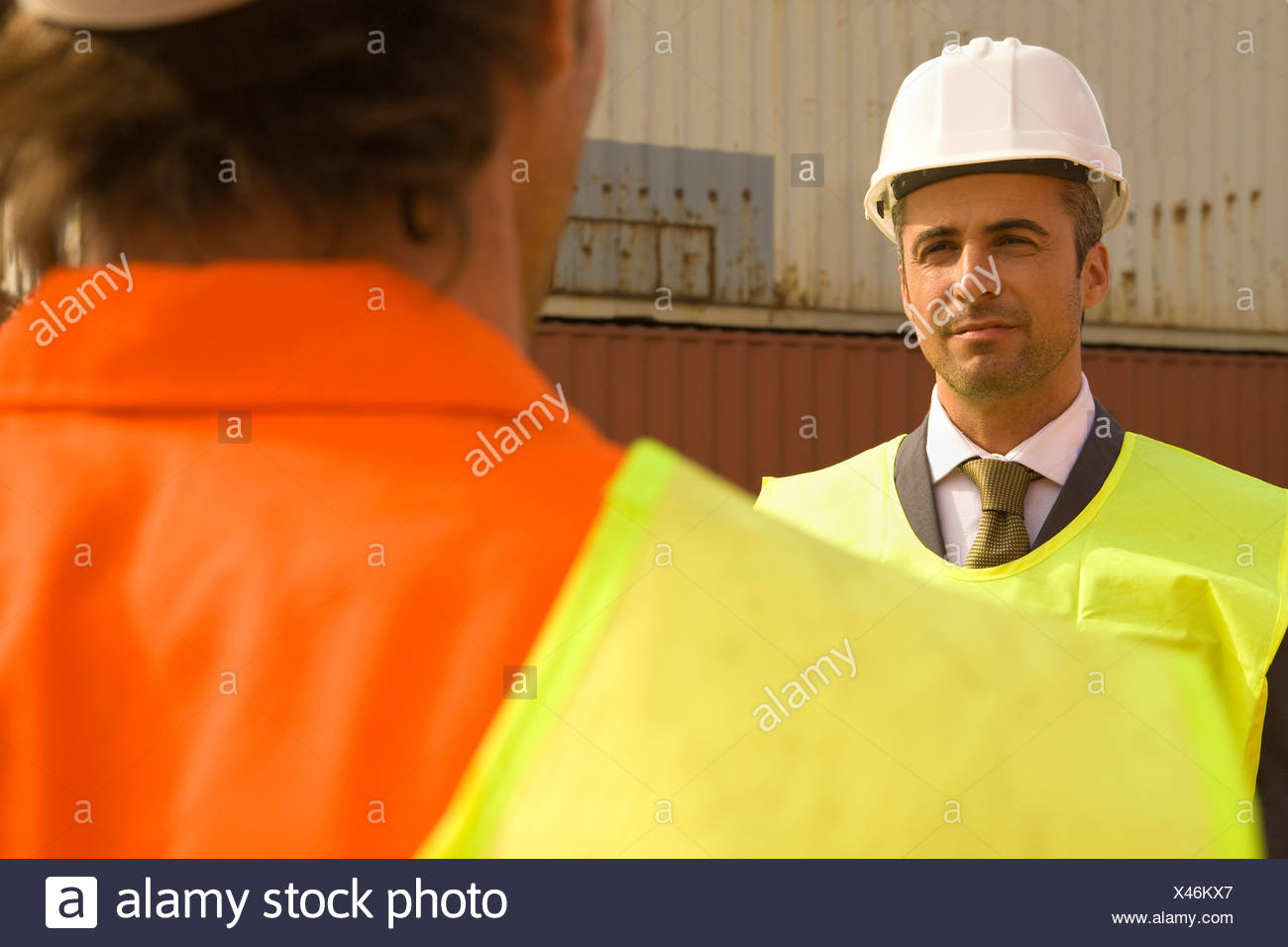 Businessman and a male dock worker wearing reflective clothing - Stock Image