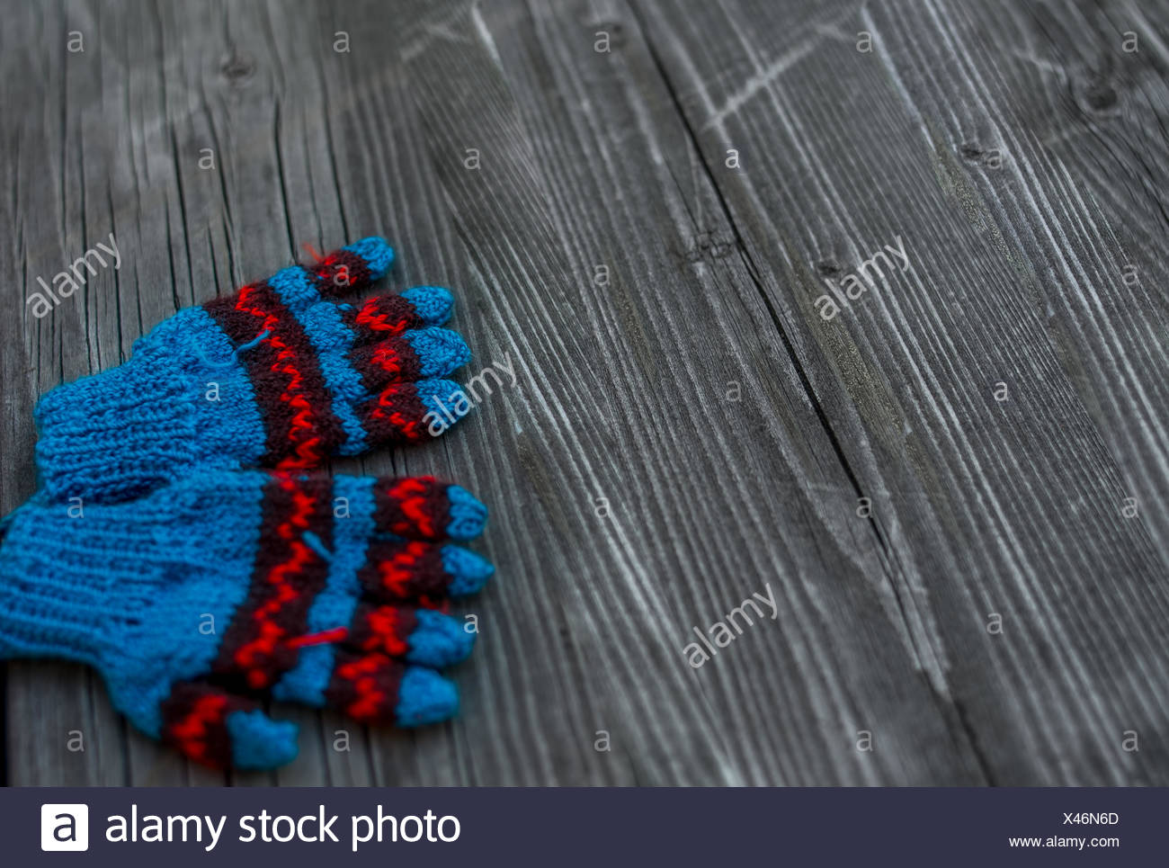 Close-Up Of Gloves On Wooden Table - Stock Image