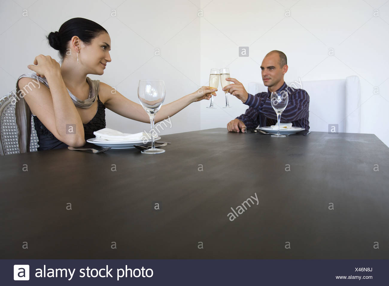 Couple sitting at table, clinking glasses of champagne - Stock Image