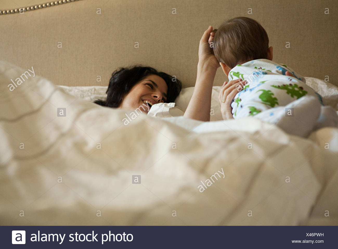 Parents and baby son having a lie in - Stock Image