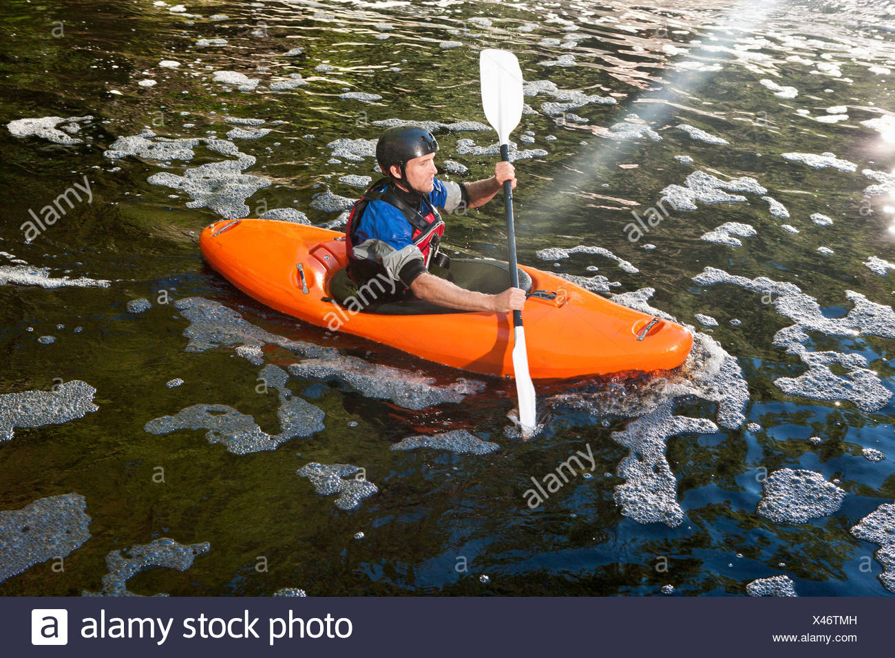 Mid adult man kayaking on peaceful river - Stock Image