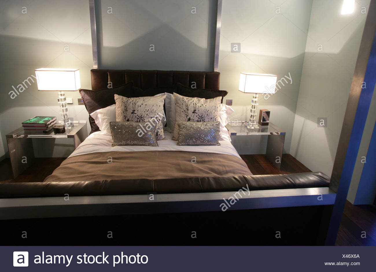 Modernist open plan home in Hampstead, London Master bedroom with four posted bed, cushions and chunky glass bedside lamps - Stock Image