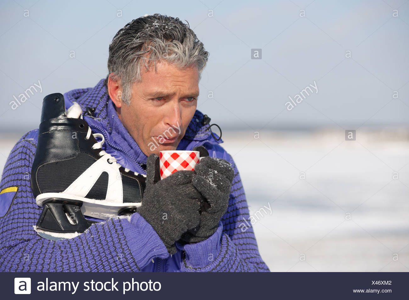 Mature man with ice skate drinking hot drink on winter day - Stock Image