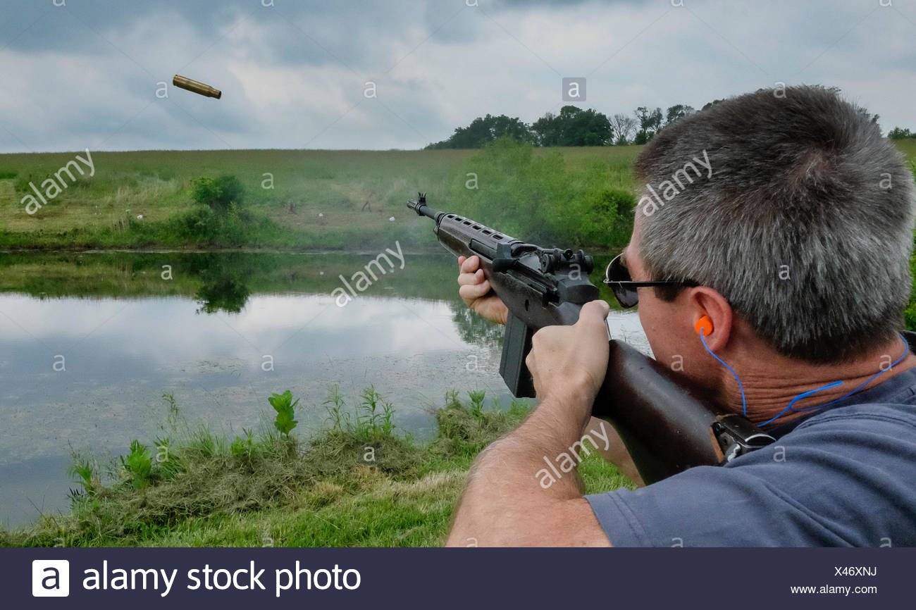 A man shoots a rifle at targets on a farm. - Stock Image