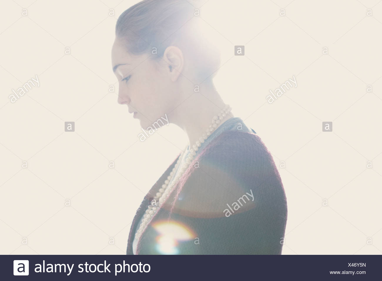 Close up head shot of young woman with sad expression with bright light - Stock Image
