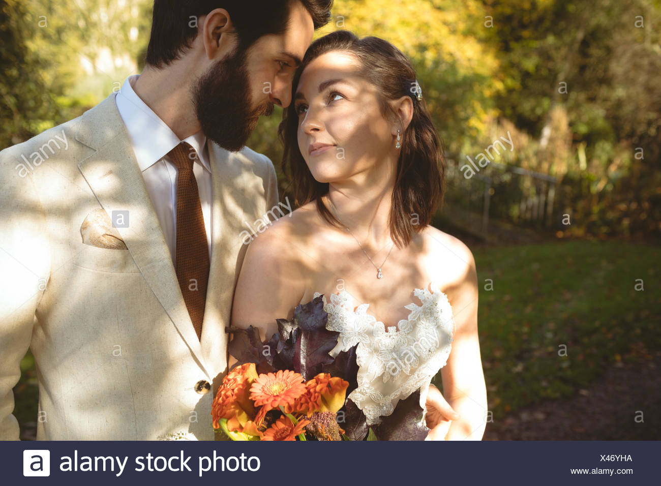 Romantic bride and groom looking into each others eyes - Stock Image
