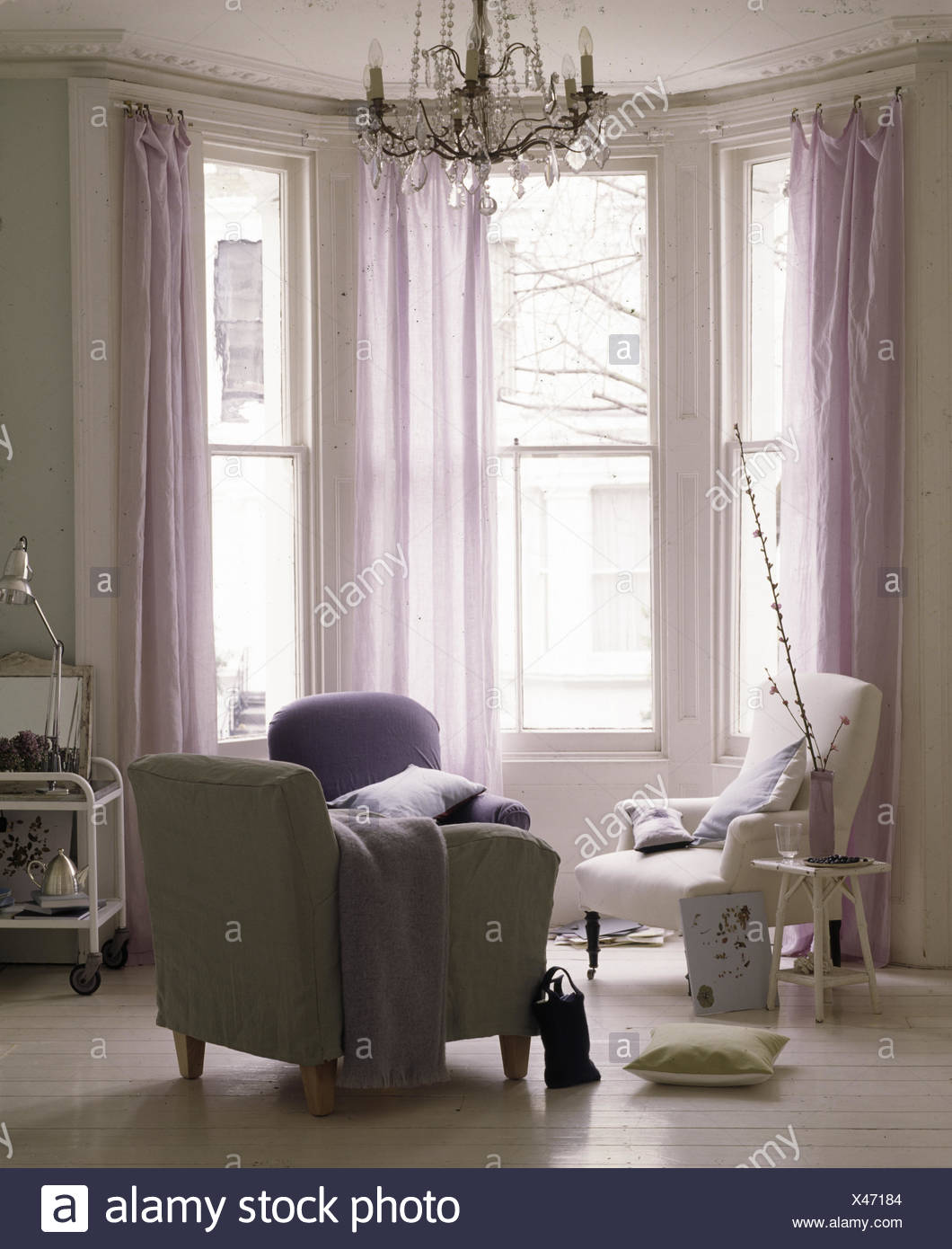 Bay Window With Sheer Mauve Curtains In Contemporary Decorated Traditional Living Room Stock Photo Alamy