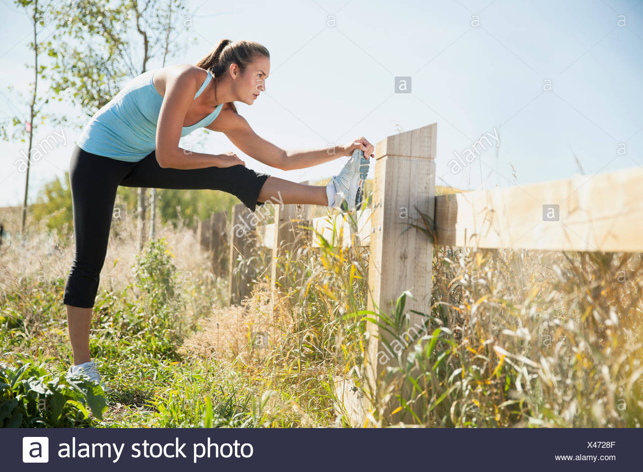 Woman stretching her leg before a run. - Stock Image
