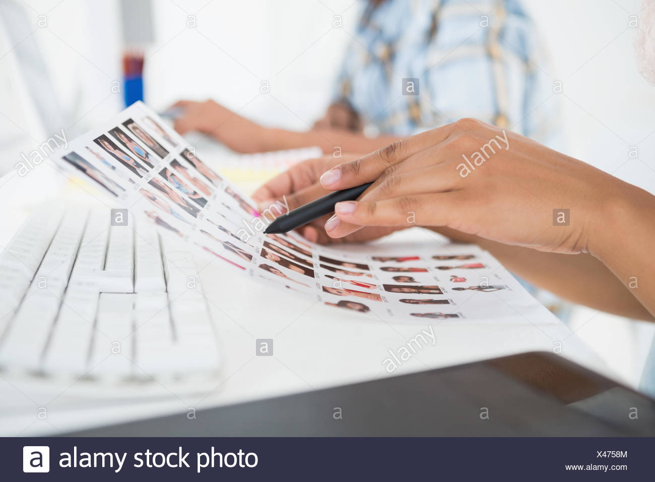 Focused young editorial team working at desk - Stock Image