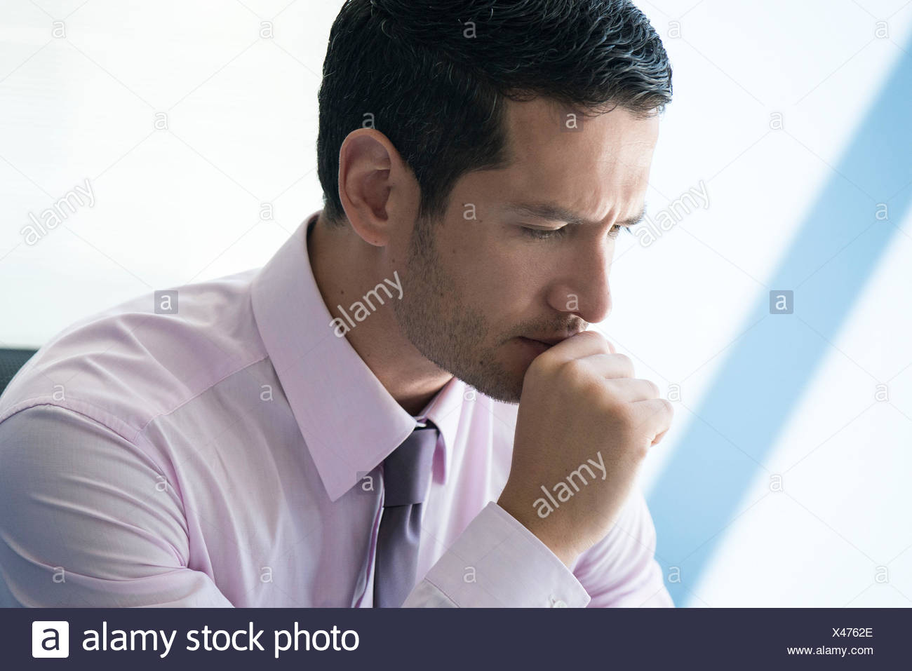 Businessman with hand under chin with look of concern - Stock Image