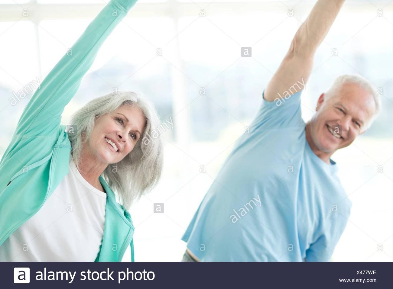 Senior couple stretching arms upwards. - Stock Image