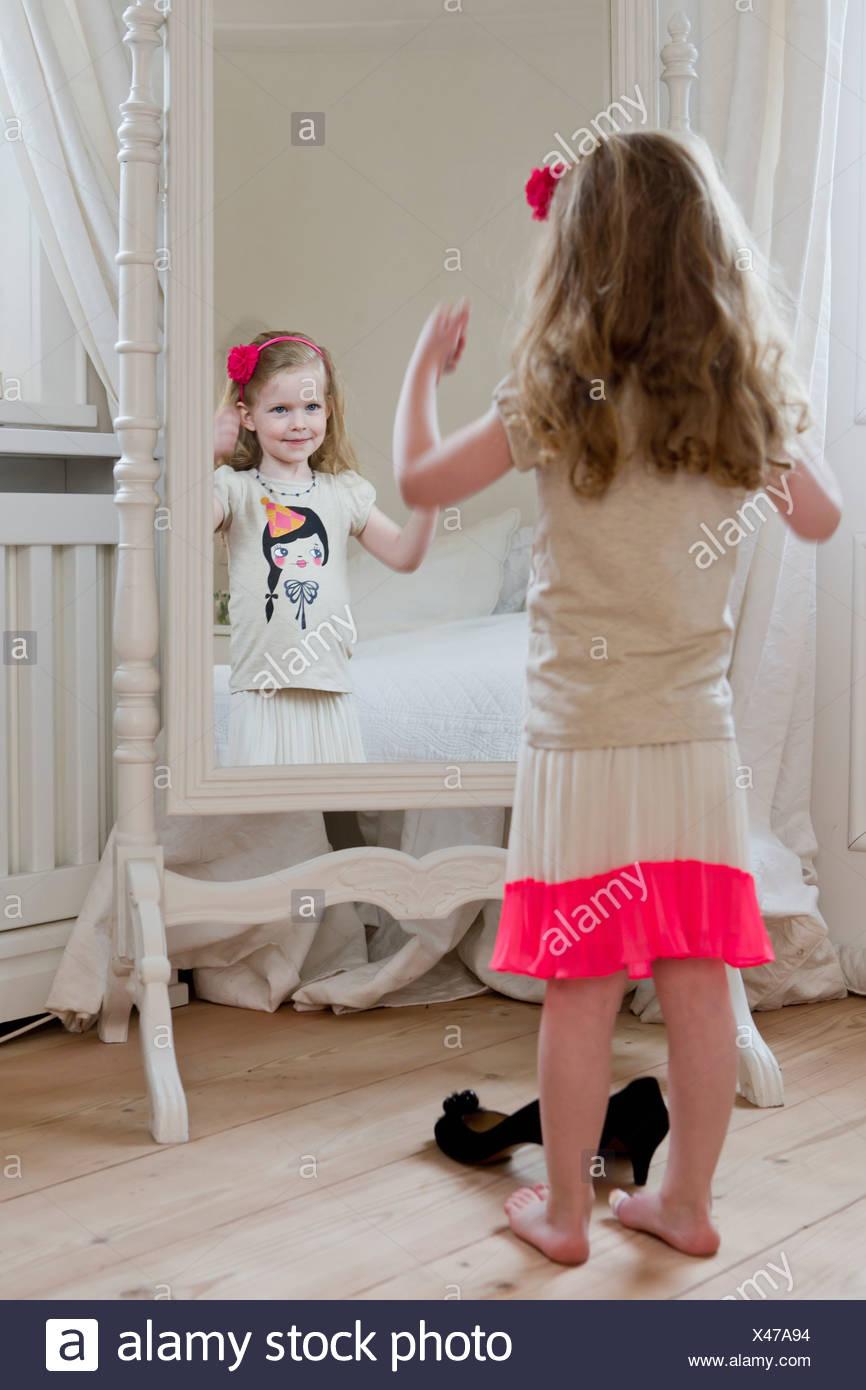 Girl admiring herself in mirror - Stock Image