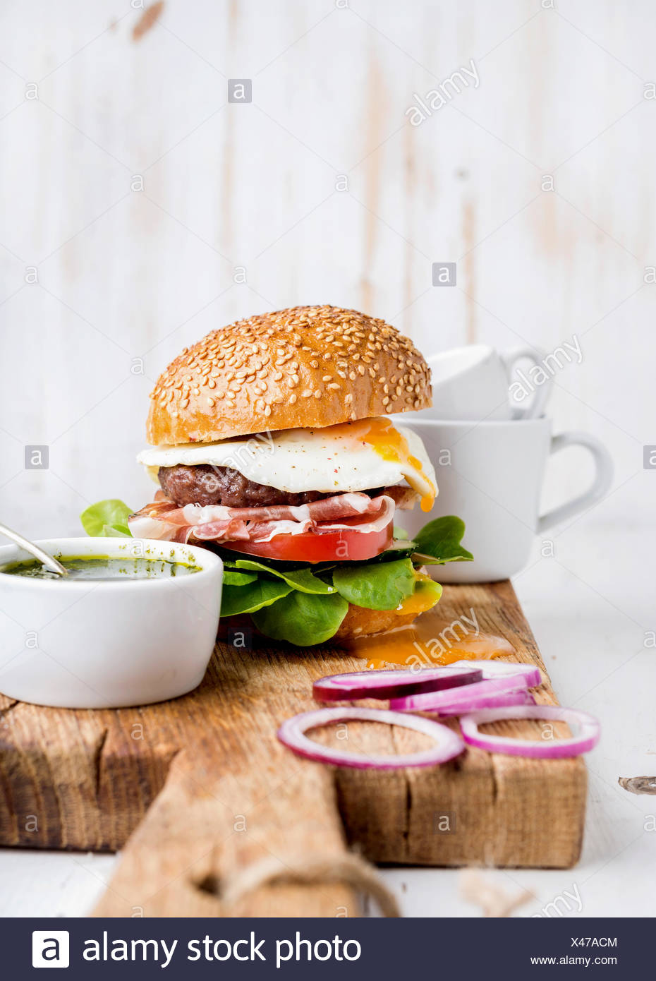 Fresh homemade burger with beef cutlet, egg, prosciutto and vegetables on wooden serving board with onion rings and pesto sauce - Stock Image
