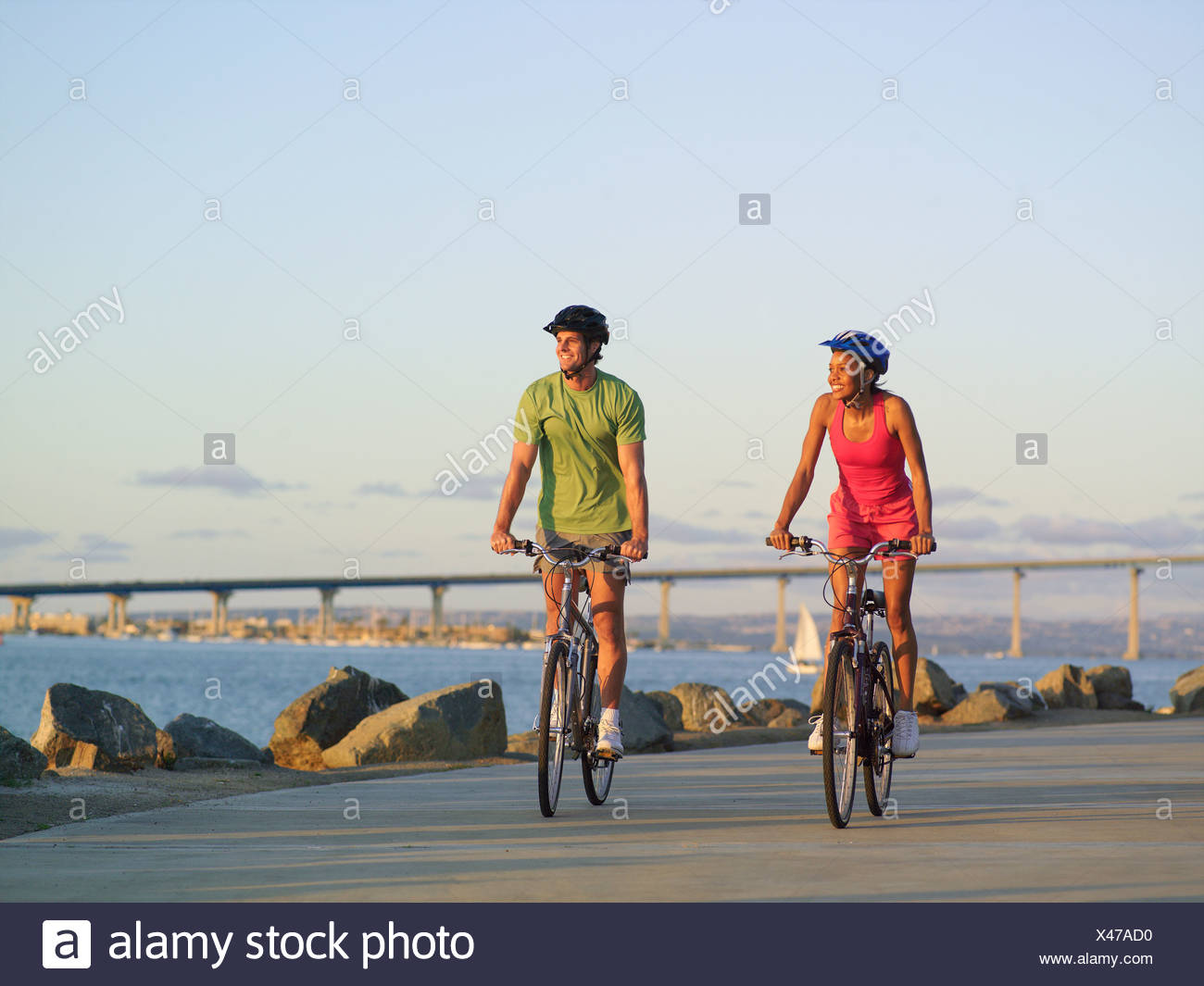 Young couple cycling on boulevard by sea at sunset, smiling - Stock Image