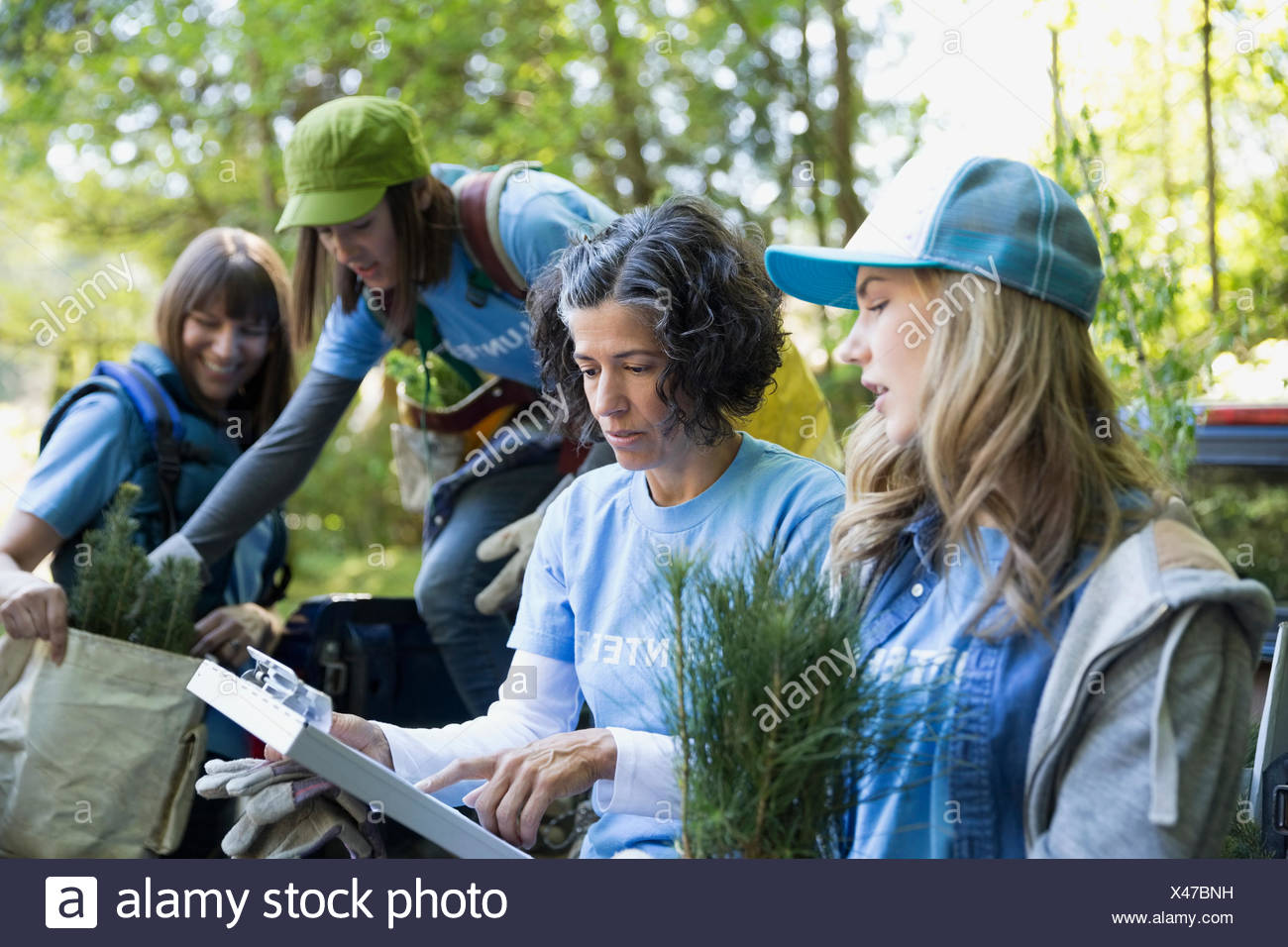Leader with clipboard guiding tree planting volunteer - Stock Image