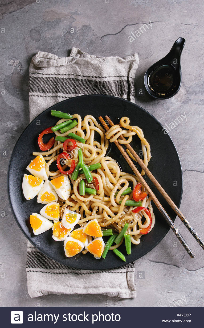 Cooking stir fry udon noodles, green beans, sliced paprika, boiled eggs, soy sauce with sesame seeds in black plate with wood chopsticks over gray tex Stock Photo