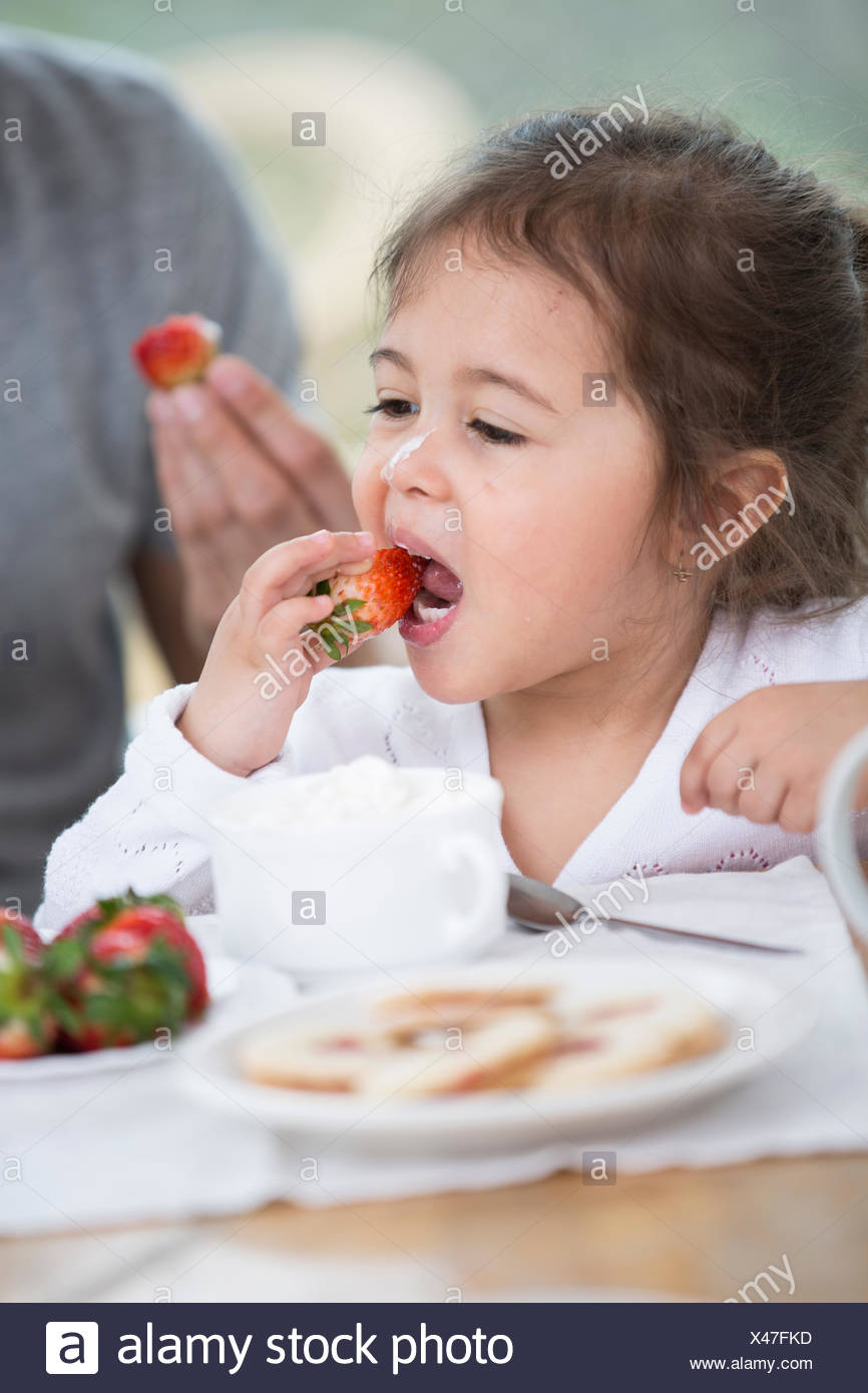 Cute little girl eating strawberry with father at breakfast table - Stock Image