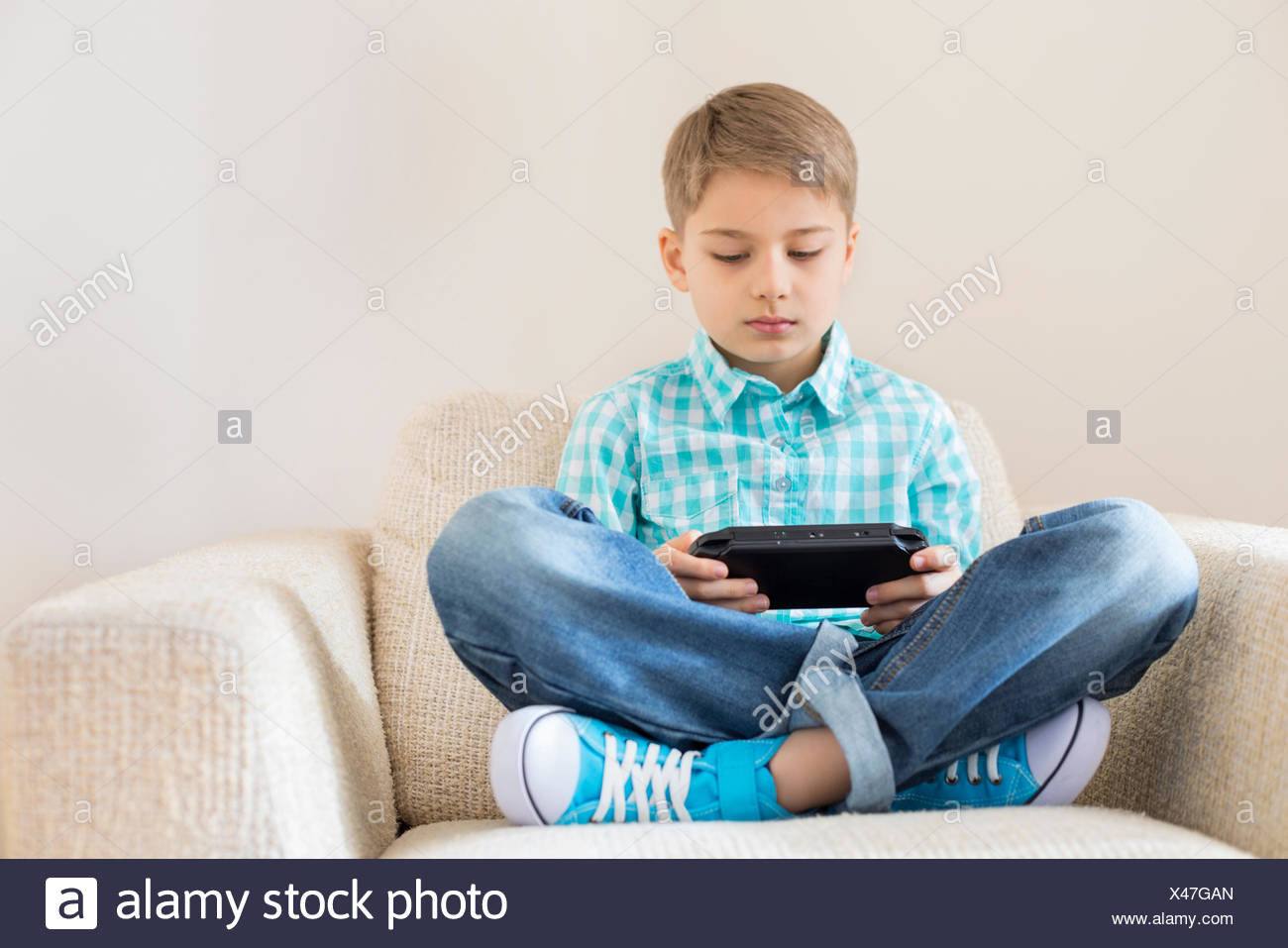 Boy playing hand-held video game on sofa - Stock Image