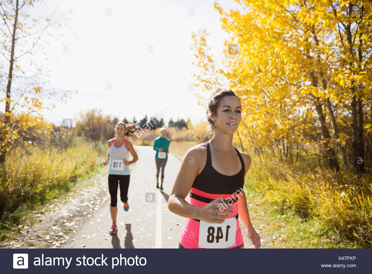 Runners racing on sunny autumn path - Stock Image