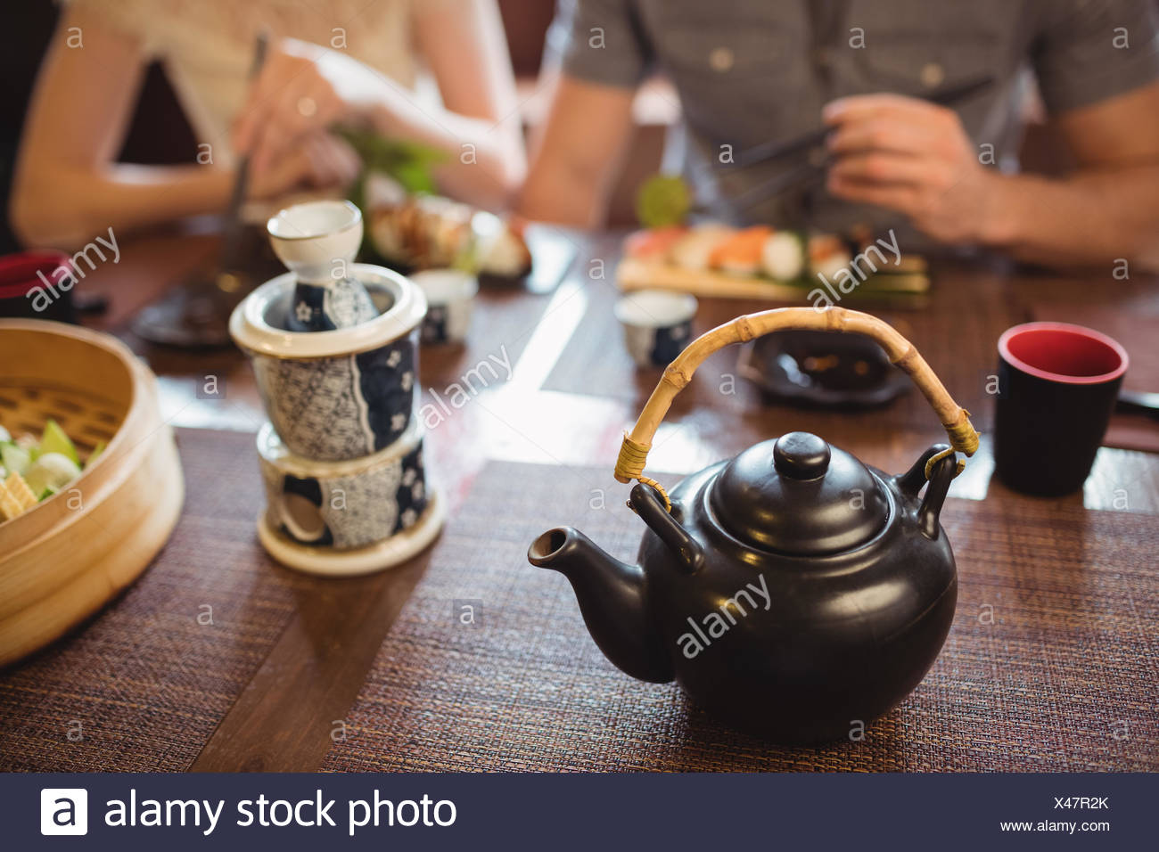 Teapot and mug on dining table - Stock Image
