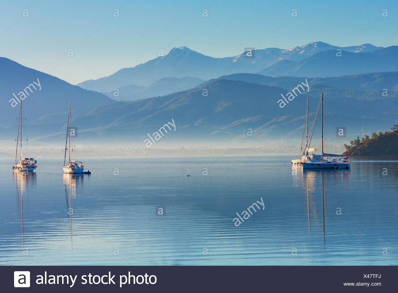 Anchored yachts at misty morning on the lake on mountains background, Fethiye, Mugla Province, Turkey Stock Photo