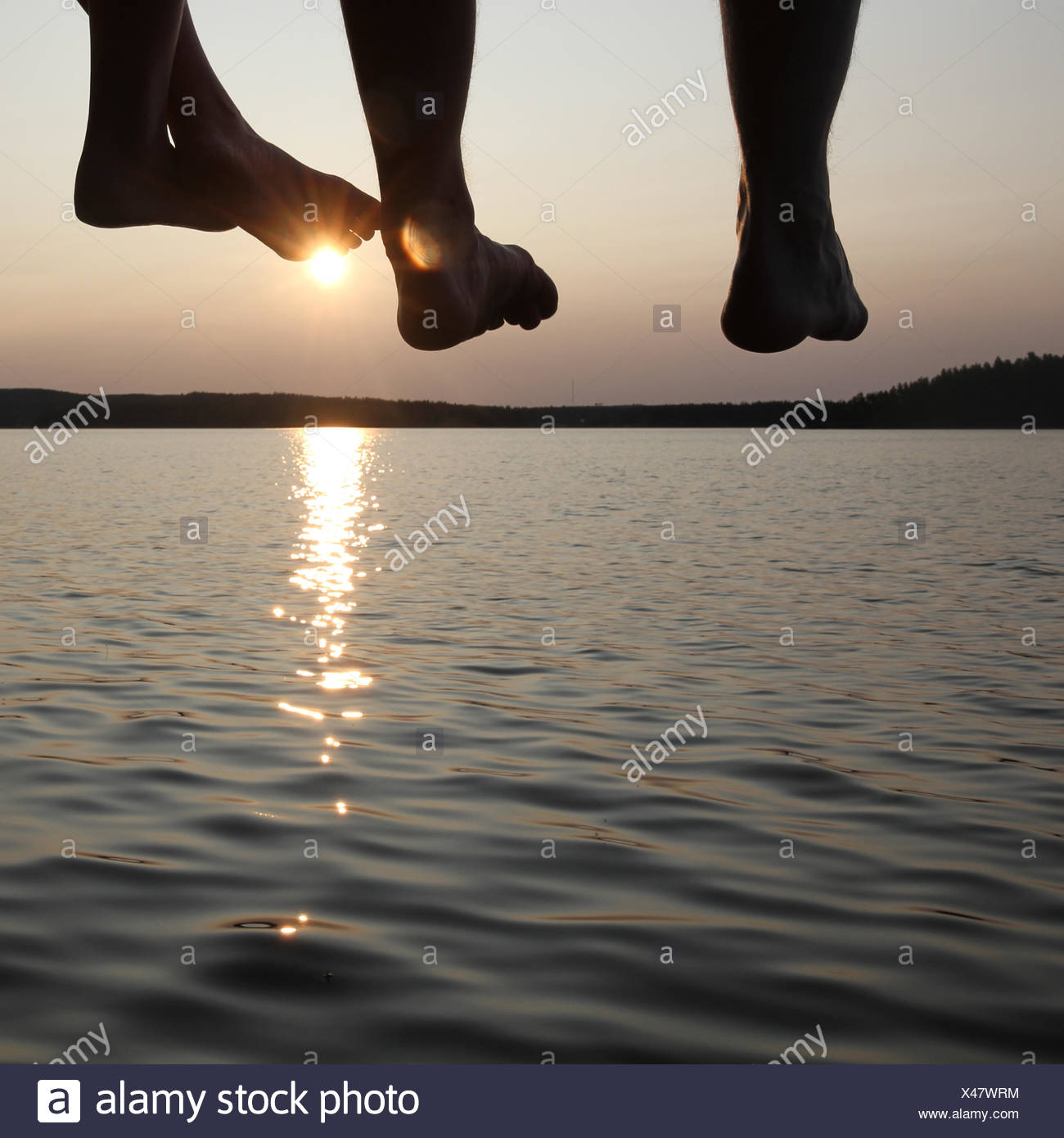 Legs dangling from a pier Stock Photo