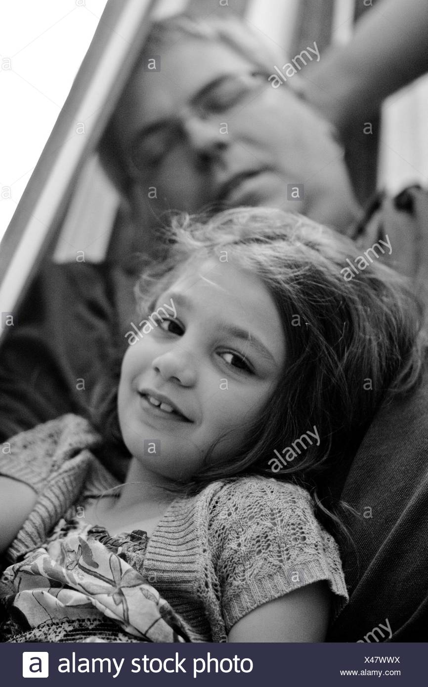 Portrait of a girl leaning against sleeping father Stock Photo