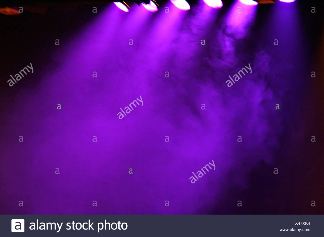 Coloured stage lights and smoke as a vivid colour background - Stock Image