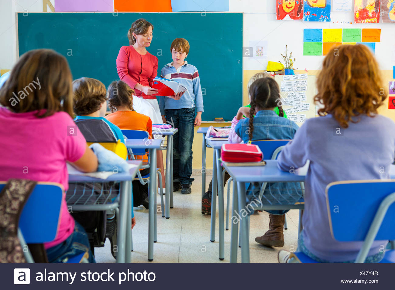 Primary schoolboy reading at front of classroom - Stock Image