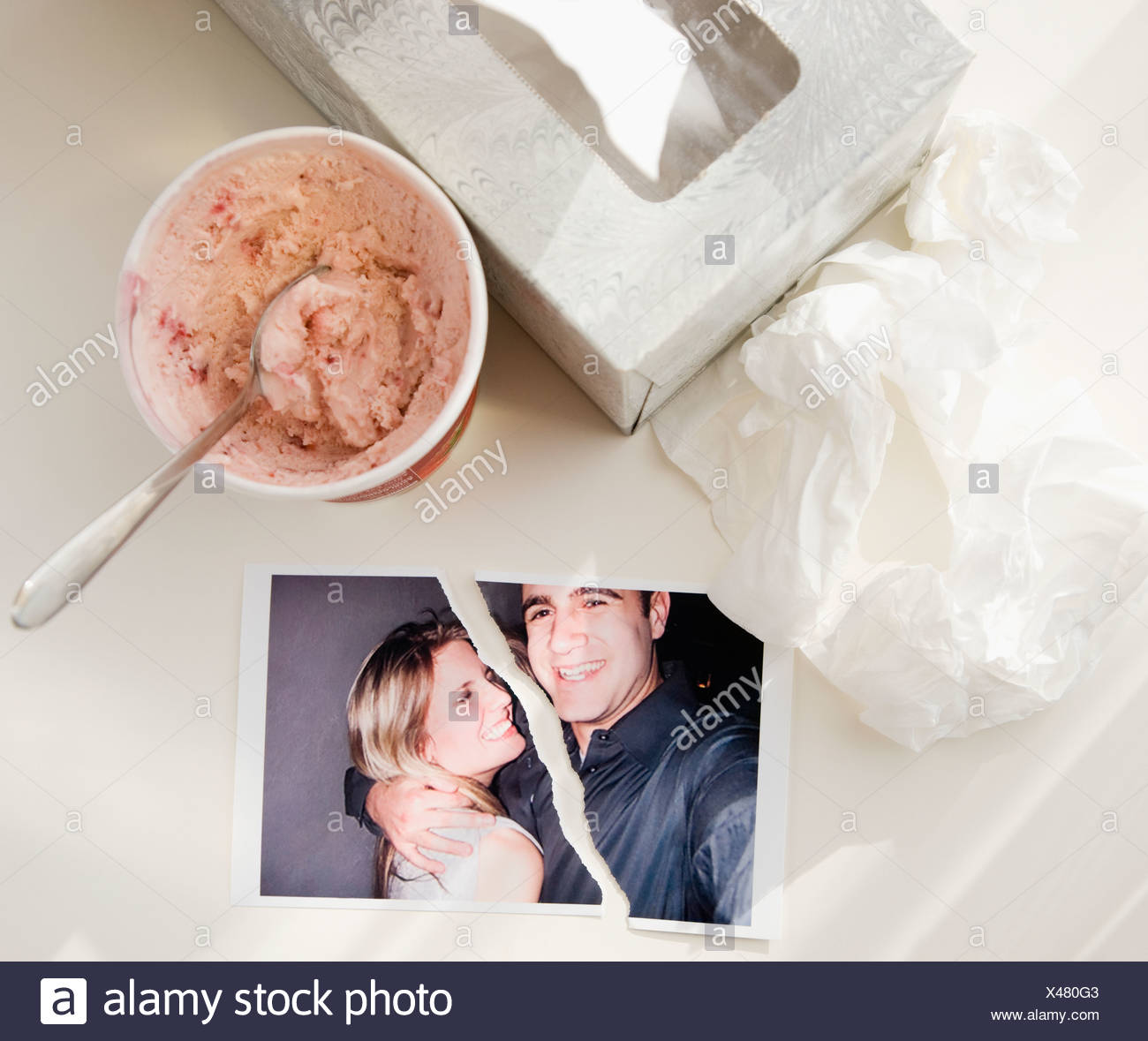 Ripped photograph next to ice cream and tissues - Stock Image