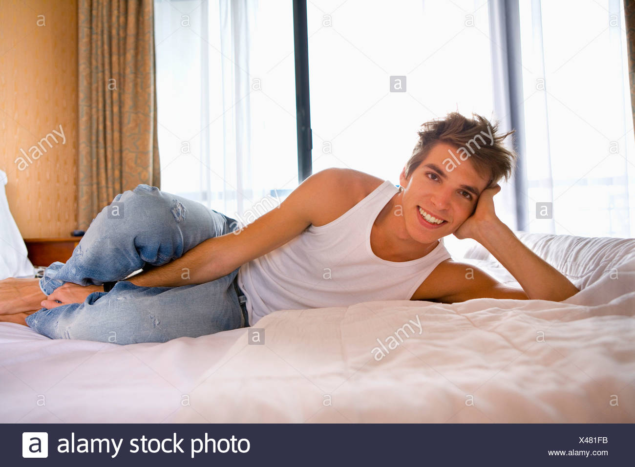 Young man smiles lays on bed. - Stock Image