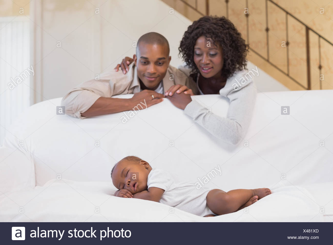 Adorable baby boy sleeping while being watched by parents - Stock Image