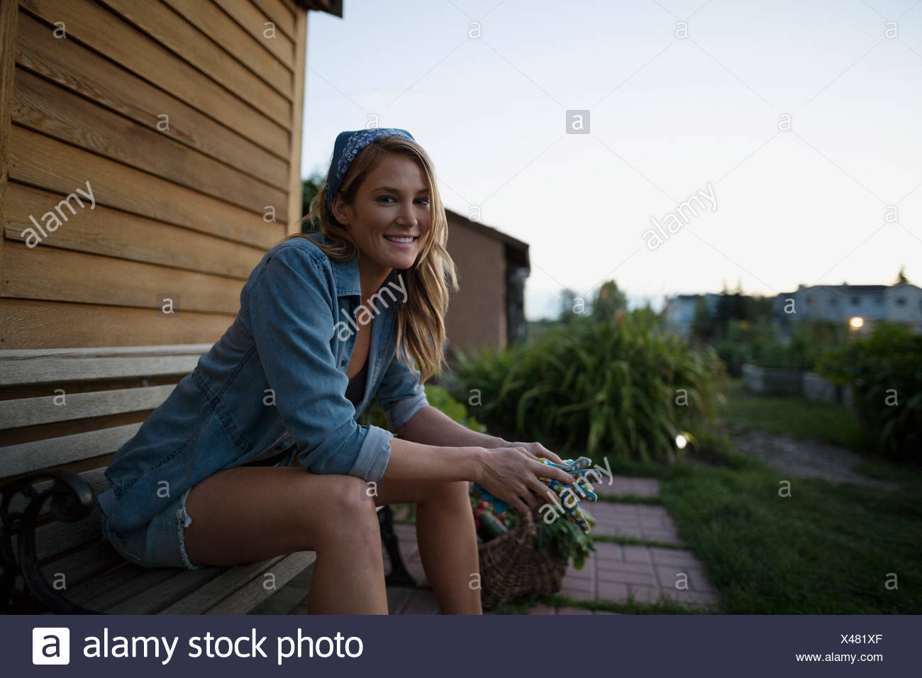 Portrait smiling woman on bench with gardening gloves - Stock Image