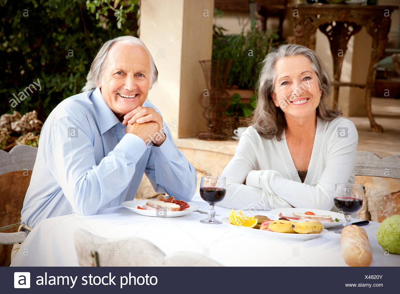 Spain, Mallorca, happy couple sitting at laid table in the garden - Stock Image