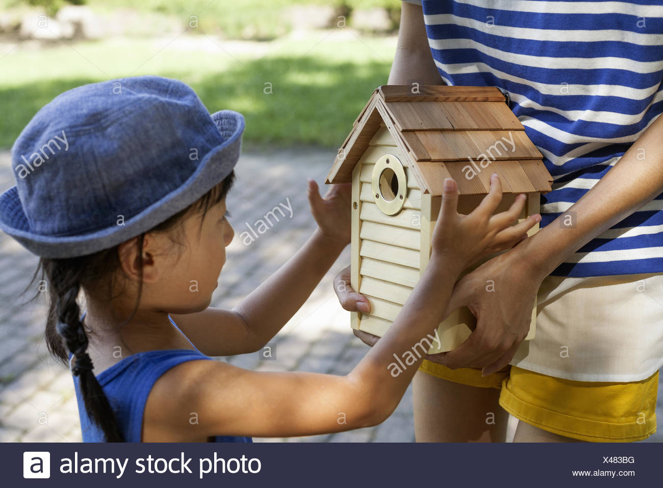 Young girl wearing a summer dress and sun hat, holding a bird house. Stock Photo