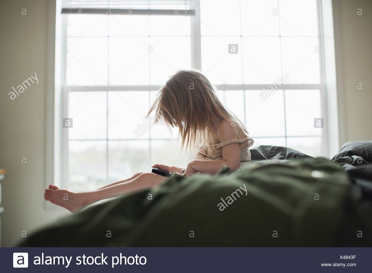 Girl sitting on bed using smartphone - Stock Image